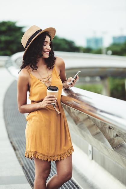 Молодая женщина, стоя на городской мост с кофе на вынос и с помощью смартфона Бесплатные Фотографии