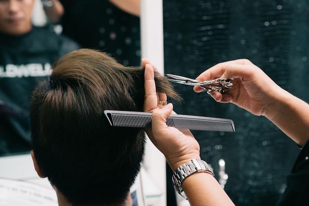 サロンで男性客の髪を切る認識できない美容師の手 無料写真