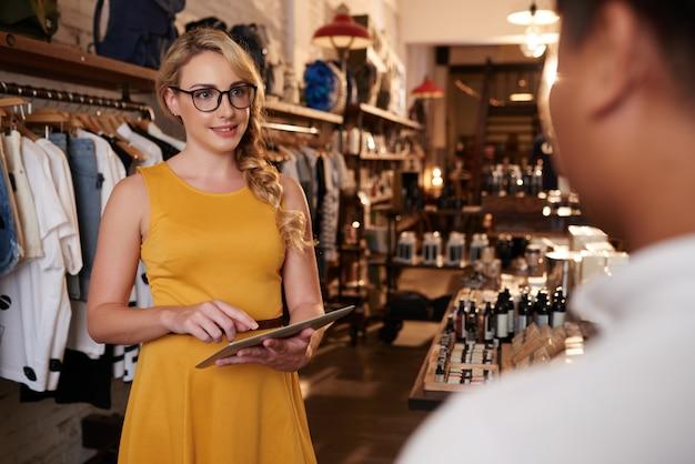 ブティック店で認識できない男と話しているタブレットで若い白人女性 無料写真