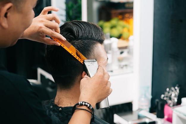 Азиатский мужской парикмахер держит расческу и триммер к голове клиента Бесплатные Фотографии
