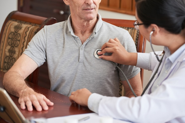 シニア患者の心拍をチェックするトリミングされた医師 無料写真