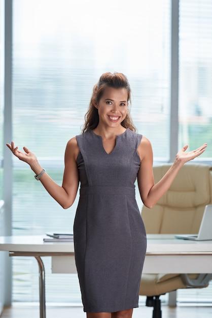 手を広げて、彼女の顔にスミとオフィスに立っている女性実業家 無料写真