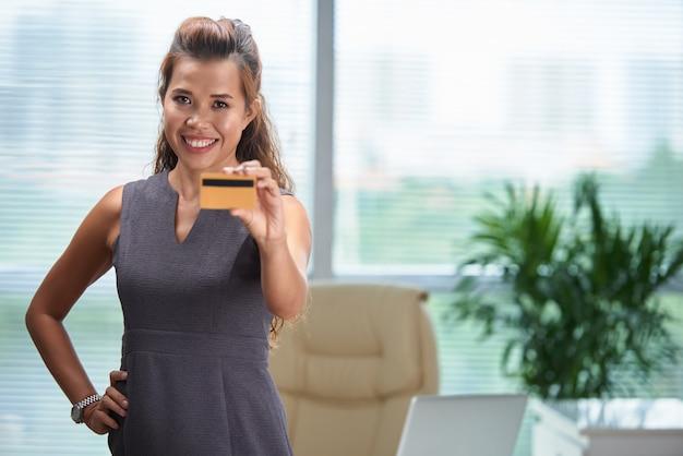 事務所に立って、クレジットカードを示す自信を持って女性のミディアムショット 無料写真