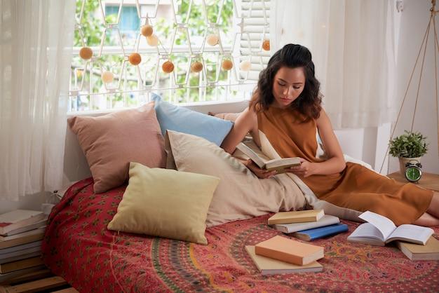 Портрет подростка девушки, чтение учебников в своей постели Бесплатные Фотографии