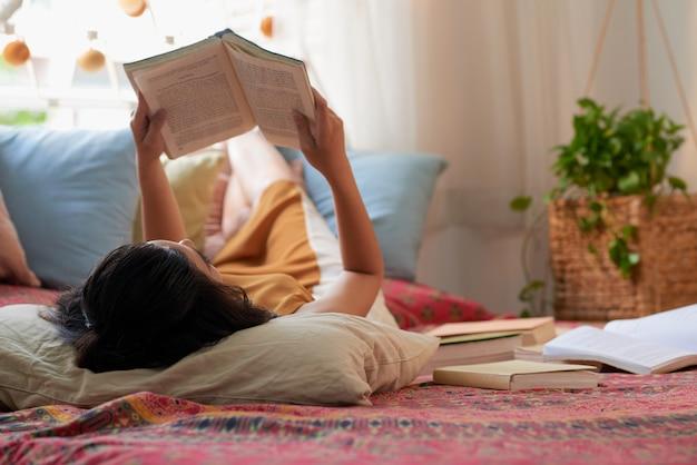 Над головой выстрел брюнетки, лежащей в кровати и читающей книгу Бесплатные Фотографии