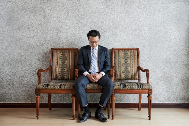 ソファに座って見下ろして大人の物思いにふけるビジネスマンのフルショット 無料写真