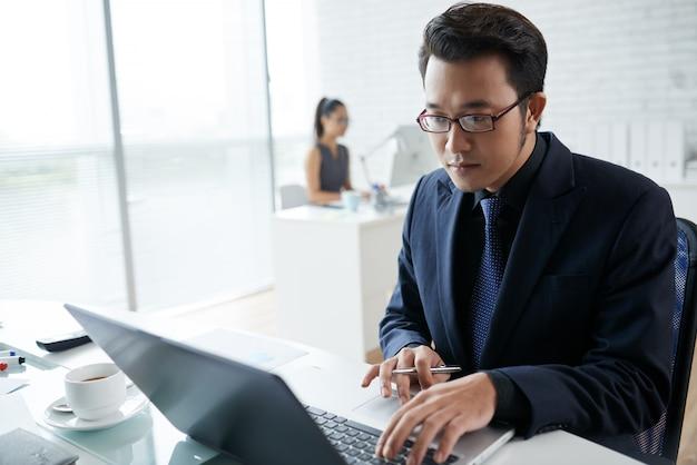 コワーキングスペースのラップトップで働くアジア系のビジネスマンのウエストショット 無料写真