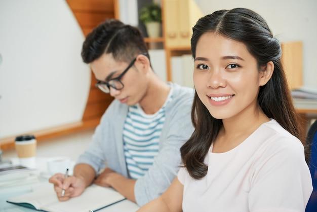 Улыбаясь азиатская женщина с коллегой-мужчиной за столом Бесплатные Фотографии