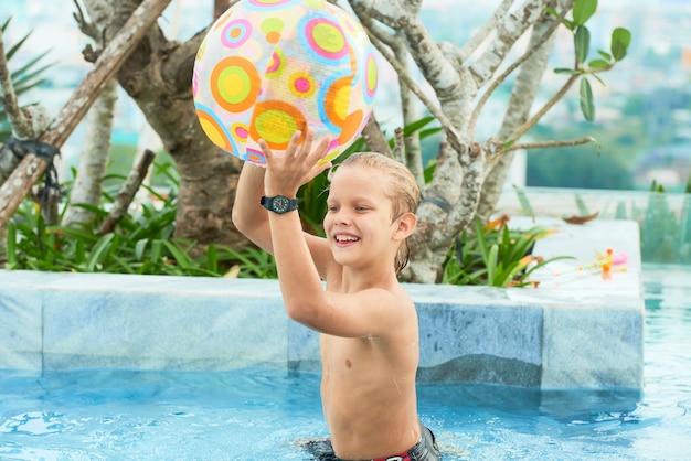 プールでボールと遊ぶ少年 無料写真