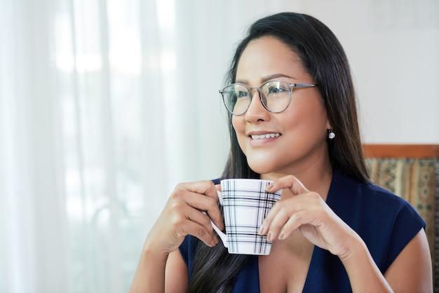 Красивая этническая деловая женщина с кружкой кофе Бесплатные Фотографии