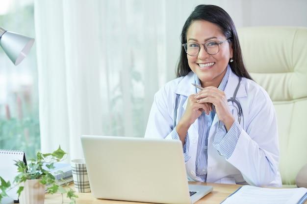 Улыбаясь этнических доктор, сидя за столом в офисе Бесплатные Фотографии