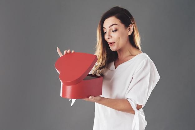 女性は赤いハート型のボックスを開きます 無料写真