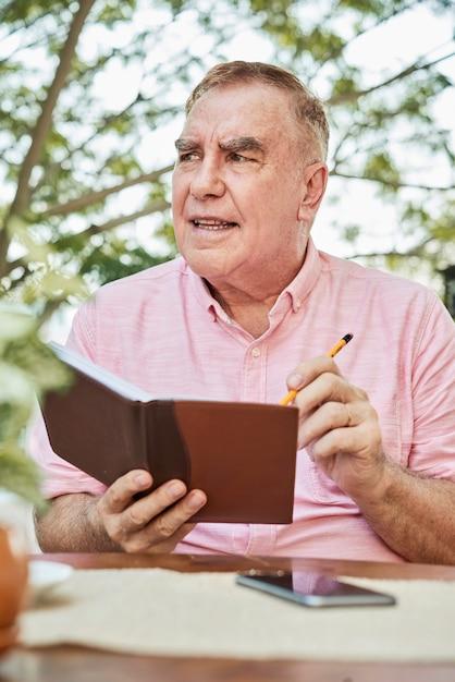 年配の男性が彼の日記を書く 無料写真