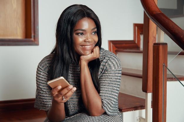 Улыбающаяся негритянка сидит с телефоном на лестнице Бесплатные Фотографии