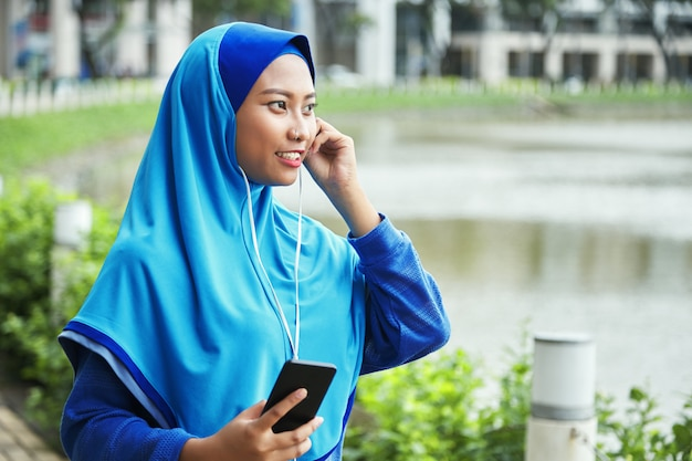 Мусульманская женщина слушает музыку на улице Бесплатные Фотографии