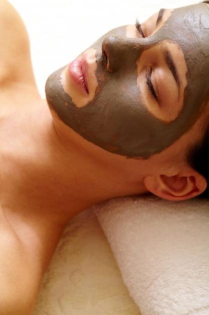 フェイシャルクレイマスクを持つ若い女性 無料写真