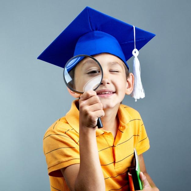 虫眼鏡と卒業キャップ付き小学生 無料写真