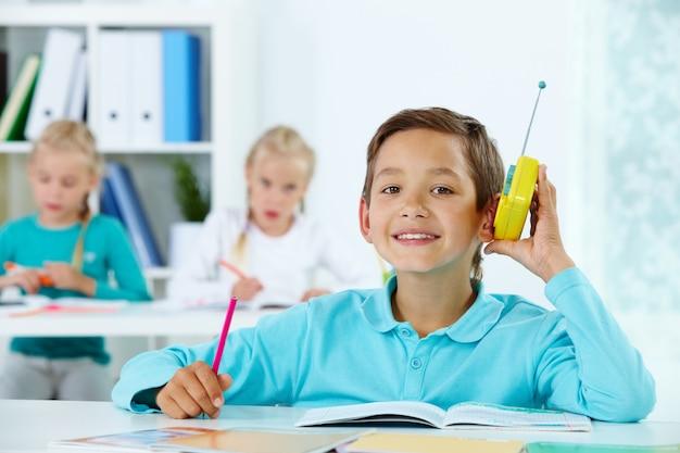男子生徒はクラスで音楽を聴きます 無料写真
