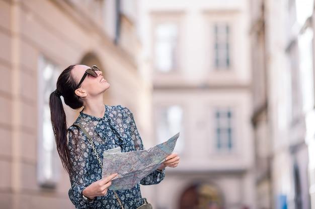Путешествие туристическая девушка с картой в вене на открытом воздухе во время каникул в европе. Premium Фотографии