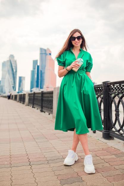 Счастливая молодая городская женщина, пить кофе в европейском городе Premium Фотографии