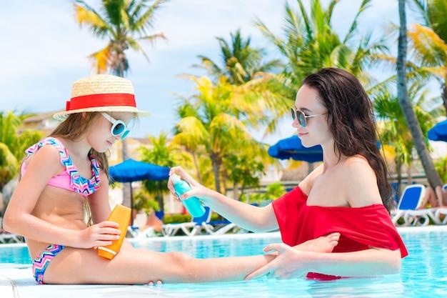 プールで娘の鼻に日焼け止めを適用する若い母親 Premium写真