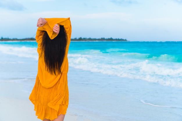日没の熱帯海岸の若い美しい女性。 Premium写真