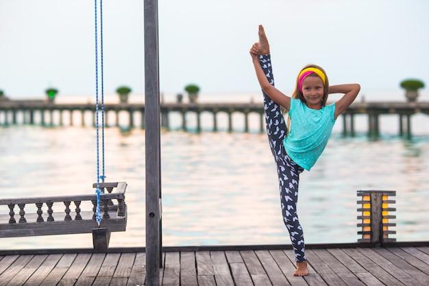 夕暮れ時の木製の桟橋に愛らしい少女のシルエット Premium写真