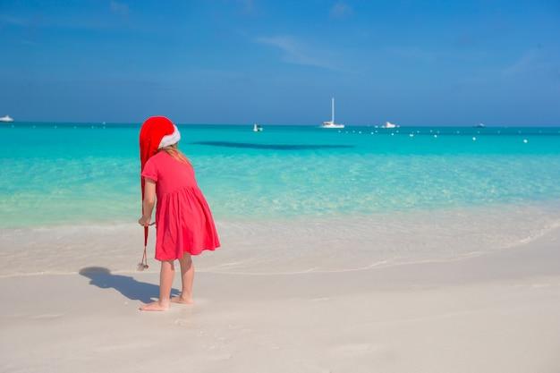 ビーチで赤いサンタ帽子でかわいい女の子 Premium写真