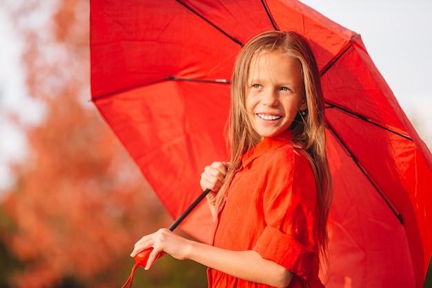 幸せな子供の女の子は赤い傘の下で笑う Premium写真