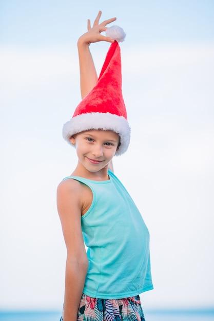 熱帯のビーチのサンタ帽子でのかわいい女の子 Premium写真