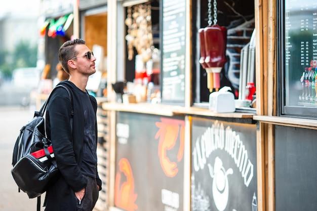 屋外のストリートフードマーケットのバックパックと若い男 Premium写真