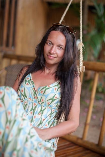 Красивая брюнетка в длинном платье расслабиться в гамаке Premium Фотографии