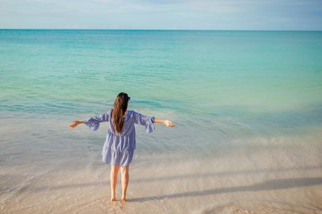 ビーチで緑のドレスの若者のファッション女性 Premium写真