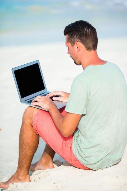 Молодой человек с планшетным компьютером во время тропического пляжного отдыха Premium Фотографии