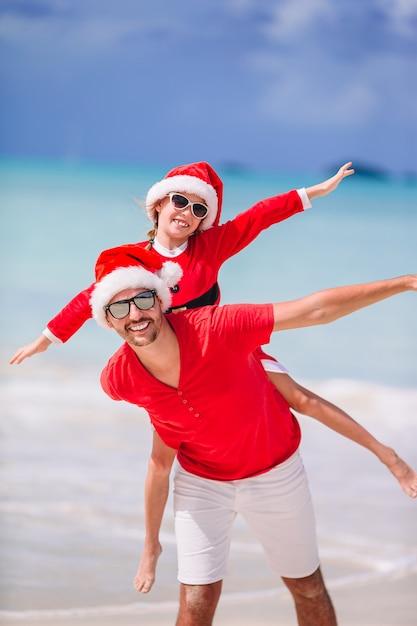 サンタ帽子の父と娘は、熱帯のビーチで楽しい時を過す Premium写真