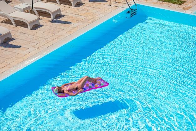 Молодая женщина в бикини надувной матрас в большом бассейне Premium Фотографии