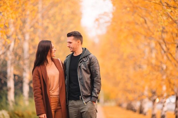 晴れた秋の日に秋の公園で歩いて幸せな家族 Premium写真