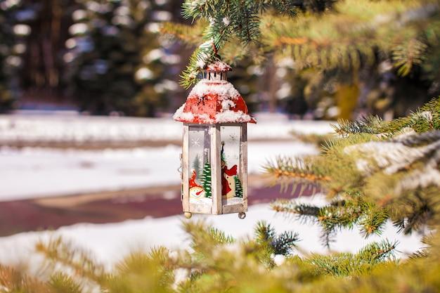 Декоративный рождественский фонарь на еловой ветке в снежный зимний день Premium Фотографии