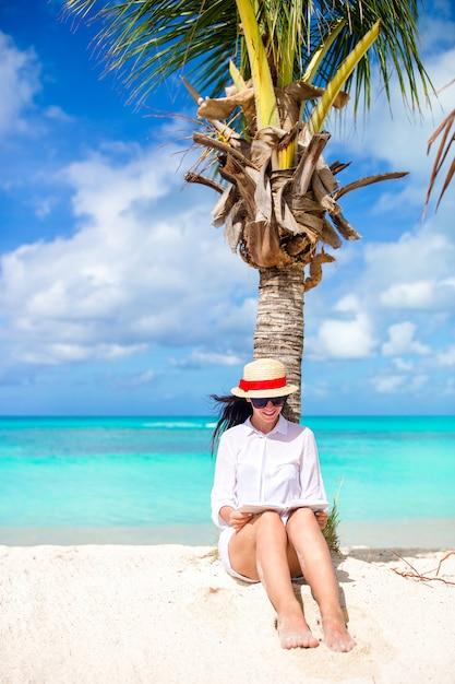 熱帯の白いビーチの中に本を読む若い女性 Premium写真