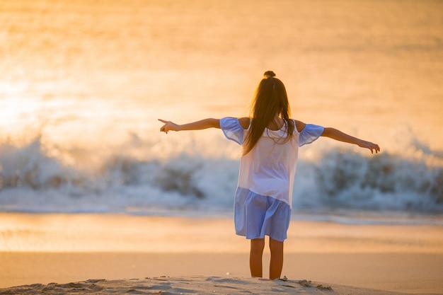 夕暮れ時の白いビーチの上を歩いて愛らしい幸せな女の子。 Premium写真
