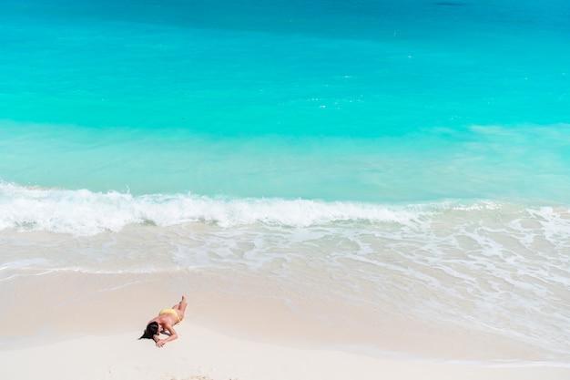 Молодая модная женщина в купальнике на пляже Premium Фотографии