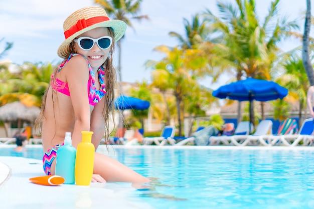 スイミングプールの端に座っているサンクリームのボトルを持つ少女 Premium写真