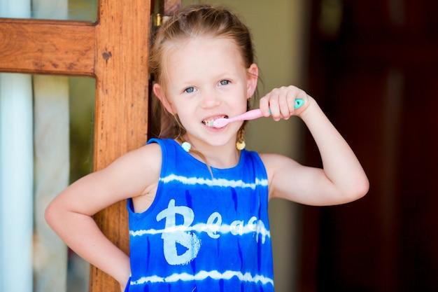 Гигиена полости рта. очаровательная маленькая улыбающаяся девушка чистит зубы Premium Фотографии