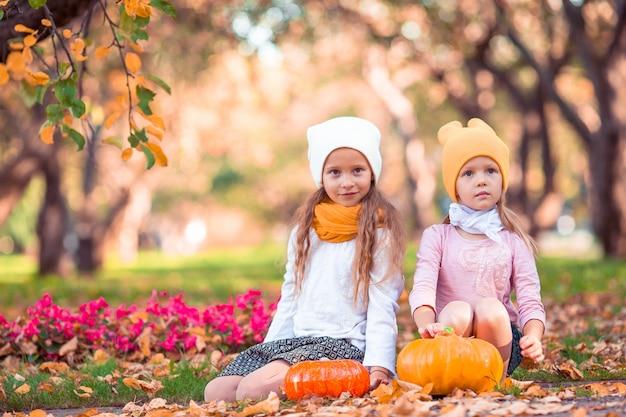暖かい秋の日に屋外でカボチャのかわいい女の子。 Premium写真