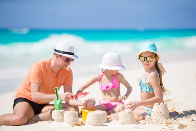 父と娘の熱帯のビーチで砂の城を作る Premium写真