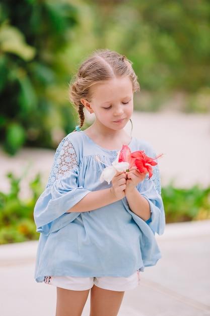 Маленькая прелестная девушка пахнущие красочные цветы в летний день Premium Фотографии