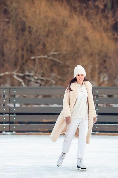 Улыбающаяся молодая девушка на коньках на катке на открытом воздухе Premium Фотографии