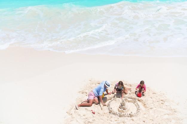 熱帯のビーチで砂の城を作る父と小さな娘の上からの眺め Premium写真