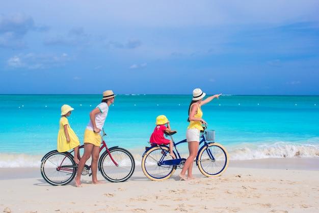小さな子供連れの若い家族は熱帯のエキゾチックなビーチで自転車に乗る Premium写真