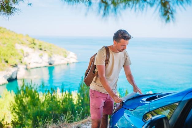 Молодой человек с картой путешествия на машине на летние каникулы Premium Фотографии
